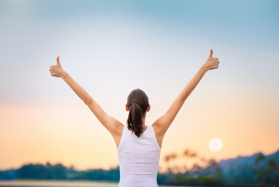 young woman with arms in the air doing a thumbs up